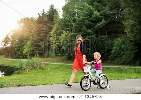 Young beautiful mother wiht her cute little daughter in nature, daughter is cycling and smilling. Slow motion.