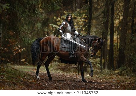 A Beautiful Warrior Girl With A Sword Wearing Chainmail And Armor Riding A Horse In A Mysterious For