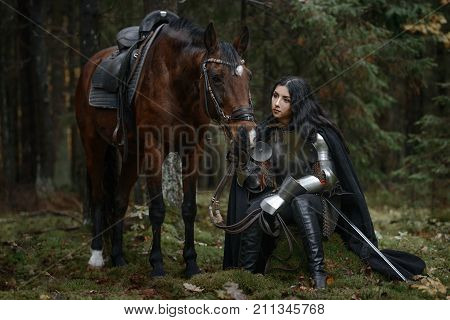 A Beautiful Warrior Girl With A Sword Wearing Chainmail And Armor With A Horse In A Mysterious Fores