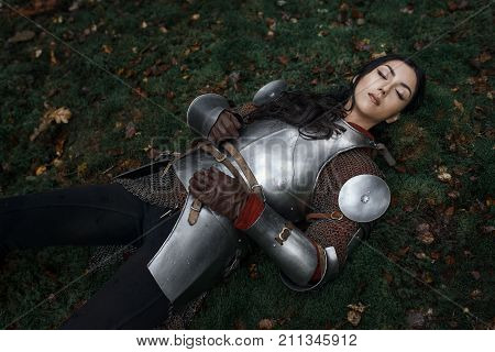A Beautiful Warrior Girl Wearing Chainmail And Armor Lying On The Ground In A Mysterious Forest.