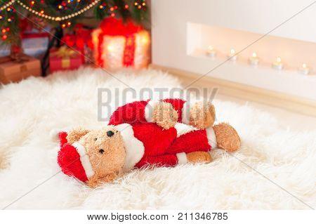 Forgotten gift. Santa teddy bear toy lie on sheepskin rug near illuminated christmas tree. Multicolored indoors horizontal image.