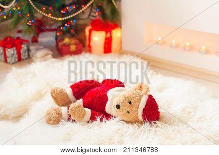 Forgotten gift. Santa teddy bear toy lie on sheepskin rug near illuminated christmas tree. Vibrant multicolored indoors horizontal image.