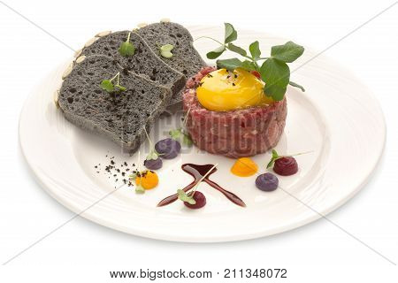 Tartar with black bread and yolk. Molecular modern cuisine. Chips Pigskin with tartare or carpaccio of beef. Stock image. Isolated on white.