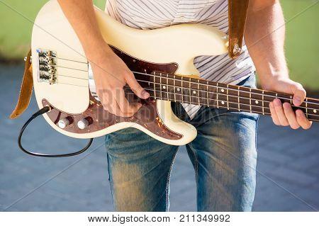 Closeup image of bass guitar player during outdoors concert