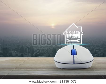 Hammer and wrench and house icon with wireless computer mouse on wooden table over modern city tower at sunset vintage style Home service concept