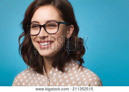 Smiling attractive brunette woman in glasses wearing dotted shirt earrings posing looking away.