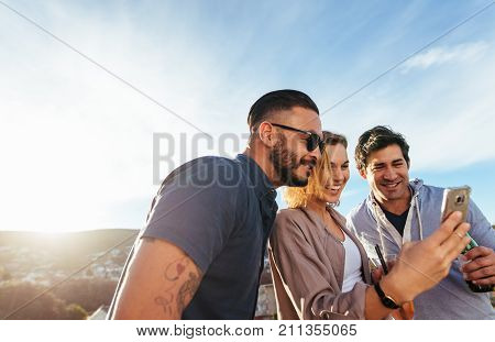 Group Of Millennial Using A Mobile Phone At Party