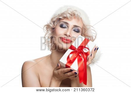Christmas Woman in Santa Hat with White Xmas Gift Box with Red Ribbon Isolated on White Background. Happy Model with Blonde Hair Makeup and Christmas Gift. New Year or Christmas Concept