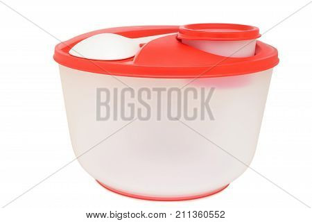 Plastic food bowl with white spoon on red lid isolated on white background