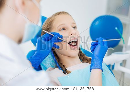 Regular checkup. Pleasant blonde young girl lying on a dental chair and opening her mouth while having a regular checkup