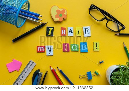 Workplace with I Hate My Job sign of carved letters and office supplies on yellow background.