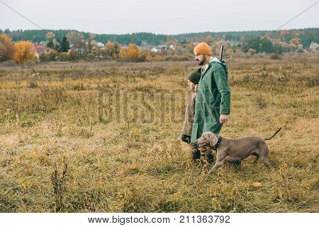 Father And Son Walking In Field With Dog