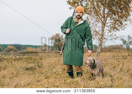 Man Walking With Dog And Gun