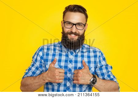 Young happy hipster man with beard wearing glasses and showing thumbs up happily on orange.