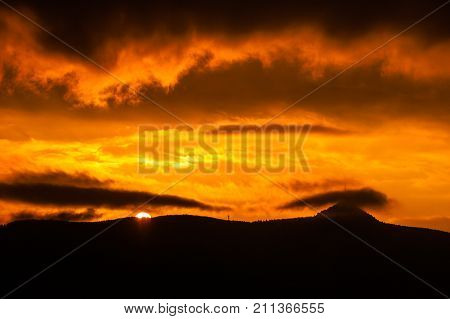 Summit and trasmitter on Jested Mountain hidden in the clouds. Dramatic red sky at sunset time. Liberec, Czech Republic.