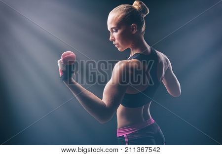 Athletic woman with dumbbells against a dark background. Woman showing her sports back