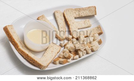Love breakfast by whole wheat bread serve with sweetened condensed milk for good health in ceramic white plate and cup isolate on wood has copy space.