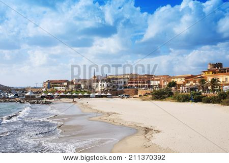 ISSOLA ROSSA, ITALY - SEPTEMBER 19, 2017; A view of the Spiaggia del Porto beach in Isola Rossa, Sardinia, Italy, with the port in the background