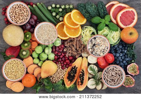Health food concept for a high fiber diet with fruit, vegetables, cereals, whole wheat pasta, grains, legumes and herbs. Foods high in anthocyanins, antioxidants, smart carbohydrates and vitamins.