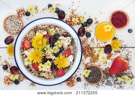 Macrobiotic health food for breakfast concept  with granola edible flowers, acai berry powder, pollen grain, berry fruit, chia seed and nuts  high in protein, omega 3, antioxidants, and vitamins.