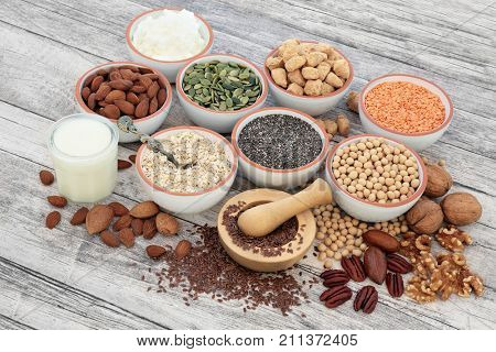Vegan health food with soy beans, seeds, nuts, soya milk, yoghurt and chunks. Foods high in fiber, antioxidants, vitamins and minerals.  On rustic wood background.
