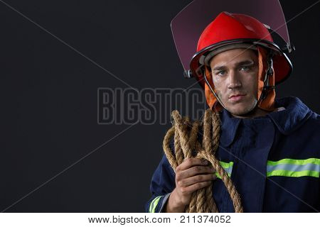 Portrait of fireman standing with a rope