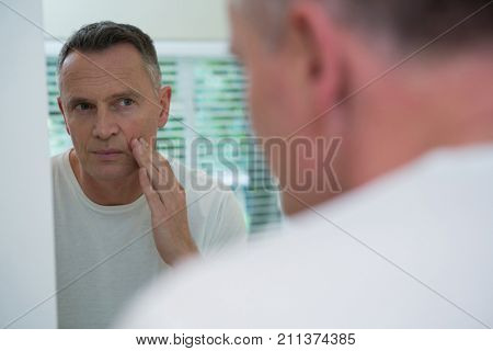 Man looking his face in the mirror after shaving standing in the bathroom