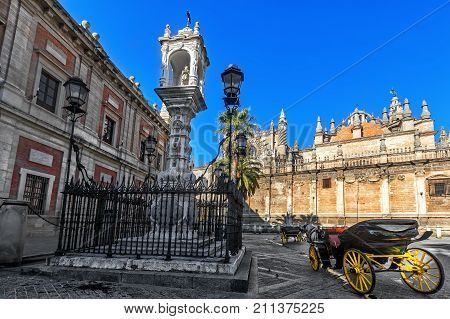 Cathedral of Saint Mary of the See (Seville Cathedral) and Traditional Horse carriage on Plaza Virgen de Los Reyes. Seville (Sevilla) Andalusia Spain.