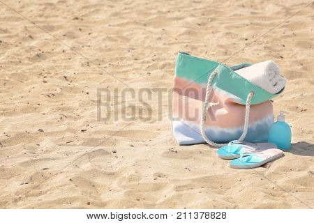 Bag with beach towel and summer accessories on sand