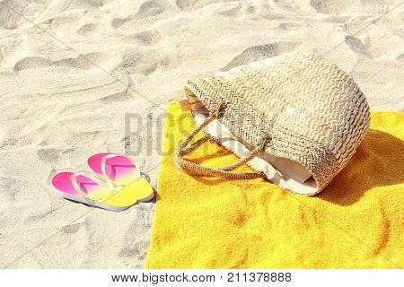 Yellow beach towel, with bag and flip flops on sand
