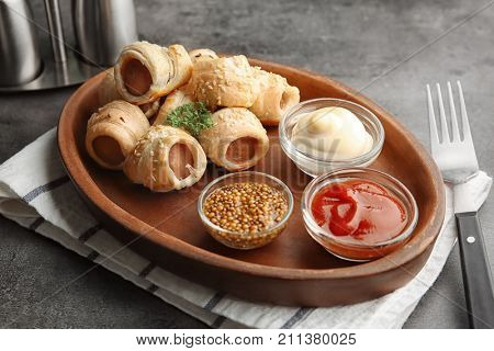 Plate with tasty sausage rolls and sauces in small bowls on table