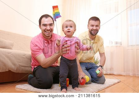Male gay couple with adopted baby girl at home