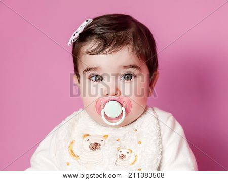 Cute, pretty and happy baby girl portrait with a pink pacifier, dummy or soother, wearing a bib and a bow in hair. Nine months old