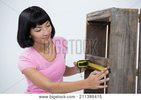 Woman measuring furniture with tape measure against white background