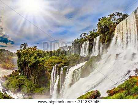 The tropical sun illuminates the seething waters. Picturesque basaltic ledges form the famous waterfalls. Waterfalls Iguazu, Argentina. The concept of active and exotic tourism