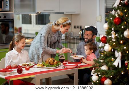 Family together at decorated table having festively Christmas dinner
