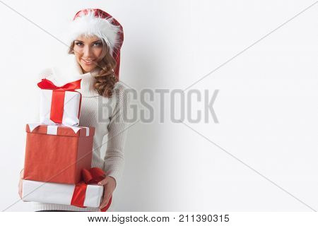 Young woman in Santa hat holding her Christmas gifts