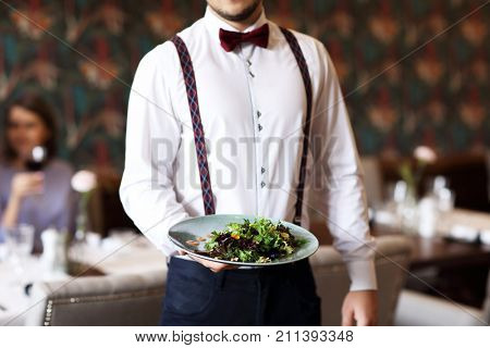Romantic couple dating in restaurant being served by waiter