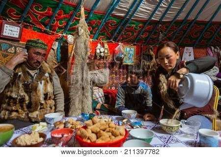 BAYAN-OLGII, MONGOLIA - SEP 28, 2017: Kazakhs family of hunters who hunt with golden eagles inside their the mongolian Yurts. In Bayan-Olgii Province is populated to 88,7% by Kazakhs.