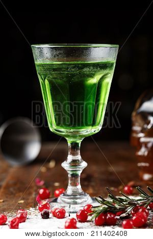 strong green alcoholic drink absinthe in a glass on the bar beside scattered berries of cranberries