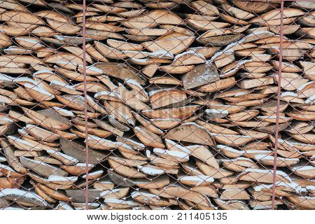 Firewood in a woodpile. Firewood under snow. Texture of firewood. It is a lot of firewood.
