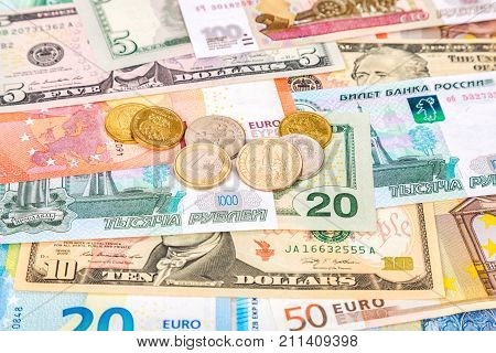 Different coins lying over different currency banknotes euro dollars and rubles close up. Money background