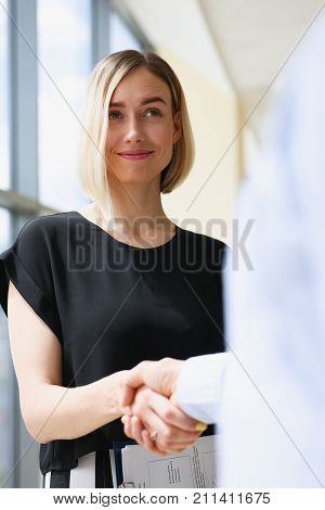 Businesswoman and woman shake hands as hello in office portrait. Friend welcome introduction greet or thanks gesture product advertisement partnership approval arm strike bargain on deal concept