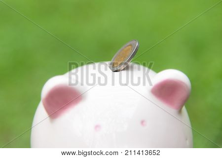 Holding piggy and putting a coin into piggy bank for future life. Investment and Saving Concept. soft and select focus