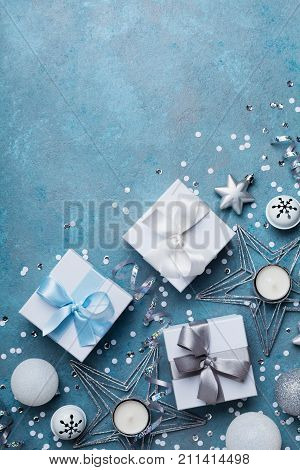 Merry christmas greeting card. Gift boxes and holiday decoration on blue table top view. Flat lay.