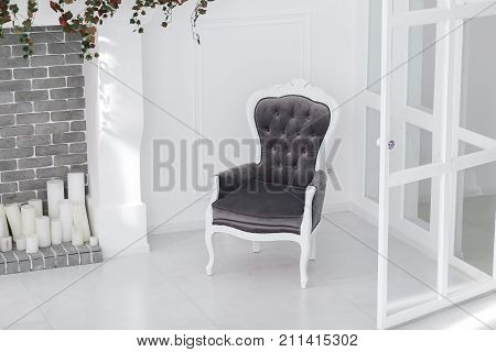 Black and white velours vintage armchair in minimalistic scandinavian room with brick fireplace and candles. horizontal photo with clear space for text.