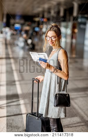 Young woman in grey dress standing with boarding passes at the departure hall of the airport waiting for the flight