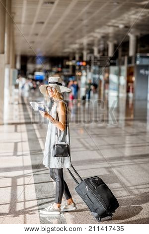 Young woman in grey dress and sunhat standing with suitcase and boarding pass at the departure hall of the airport during the summer vacation