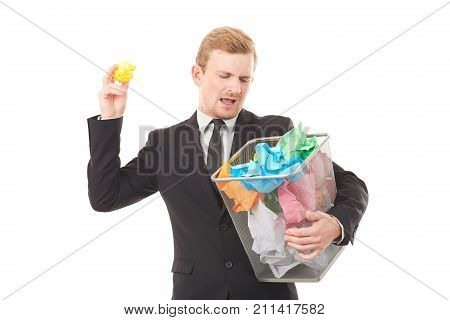 Portrait of businessman searching document in paper basket among crumpled papers