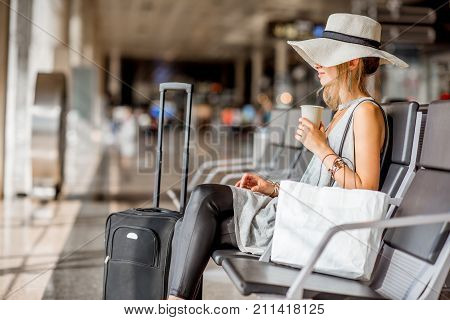 Young woman in sunhat sitting with laggage and shopping bag at the departure hall of the airport during the summer vacation